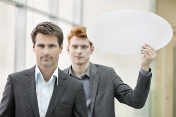 Portrait of a businessman with his colleague holding a speech bubble behind him