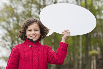 Portrait of a boy holding a speech bubble