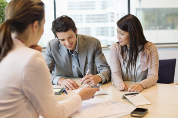 Couple signing documents with business executive
