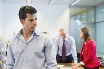 Male executive listening to his colleagues conversation in an office