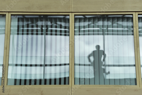 Reflection of a person on the glass of an office window