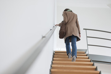 Rear view of a woman moving up staircase