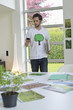 Man using a mobile phone with environment related posters in front of him on a table