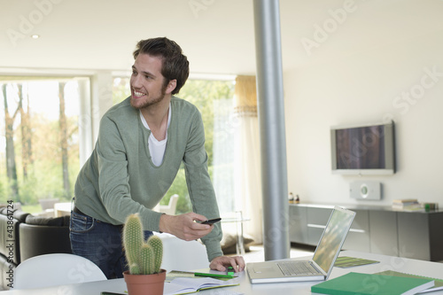 Man holding a mobile phone and working on a laptop