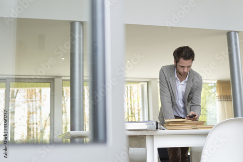 Interior designer using a mobile phone in the office
