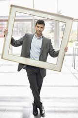 Businessman holding a frame in an office lobby