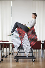 Businesswoman sitting on pileup chairs in an office