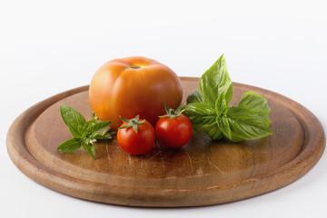 Pomodoro, pomodorini e basilico su tagliere