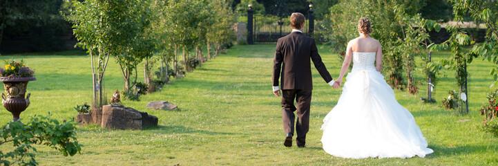 brautpaar schlendert hand in hand durch einen park