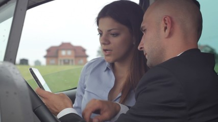 Young businesspeople work with tablet in car