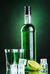 bottle and glasses of absinthe with lime and ice