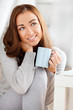 attractive young woman drinking coffee at home