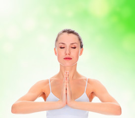 young girl practicing yoga, meditating in prayer pose