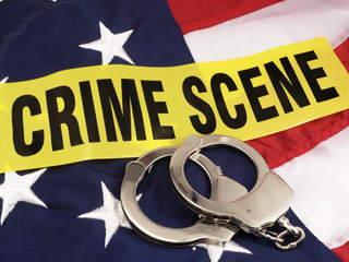 Crime Scene Tape And Hand Cuffs Over American Flag