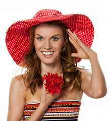 Young beautiful woman in red hat with red flower