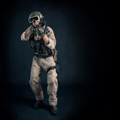 Soldier with rifle against black background. Full body