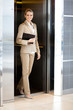 beautiful young businesswoman walking out elevator