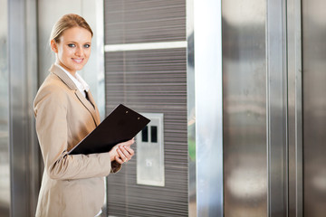 young businesswoman waiting for elevator in the building