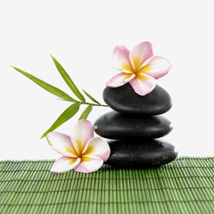 Spa stones and frangipani and a bamboo leaf on green mat