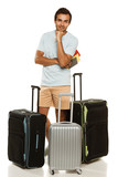 Full length of man standing with three travel suitcases