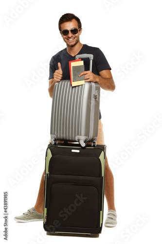 Full length of male with suitcases, tickets and passport