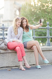Two women using digital camera smiling