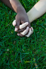 Multiracial couple holding hands on the grass