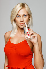 Woman in bright red dress holding a glass of water