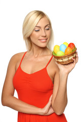 Female holding basket with Easter eggs, looking at the basket