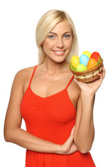 Smiling female holding basket with Easter eggs
