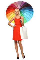 Female standing under rainbow umbrella, holding shopping bag