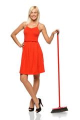 Full length of smiling woman standing with broom