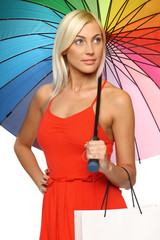 Female in red under rainbow umbrella, holding shopping bag