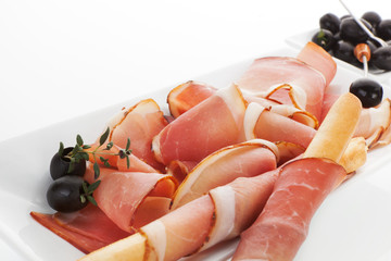 Prosciutto slices with black olives.