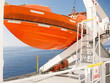 Orange lifeboat on deck of cruise ship