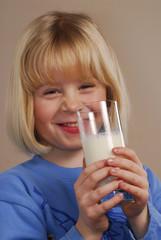 Niña feliz bebiendo un vaso de leche.