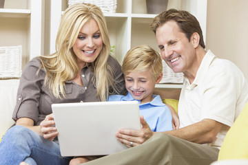 Happy Family Sitting on Sofa Using Laptop Computer