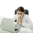 young brunette business woman is ill with hankies behind laptop