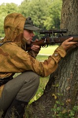 man in form of nazi sniper aims near a tree