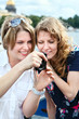 Two beauty women looking at screen of simple hand-held camera