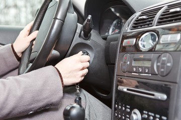 Woman caucasians hand starting a car engine with ignition key