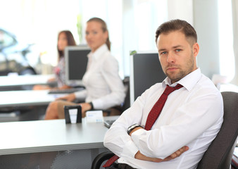 Businessman sitting at desk using computer with colleagues