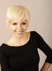 Beautiful young woman with short blond hair looking at camera