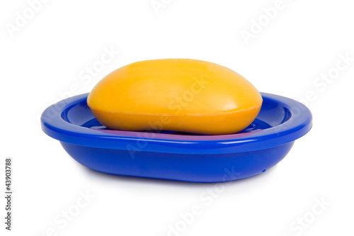 Soap of yellow color in a dark blue soap tray