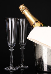 Champagne bottle in bucket with ice and glasses isolated