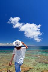 南国沖縄の海辺でリラックスする女性