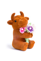 Side macro shot of cute little loved bull toy with bouquet of fl