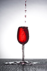 Rotweinglas läuft über