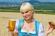 Junge Frau im Dirndl mit Bier und Brezel
