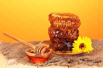 Honeycomb on wooden table on orange background
